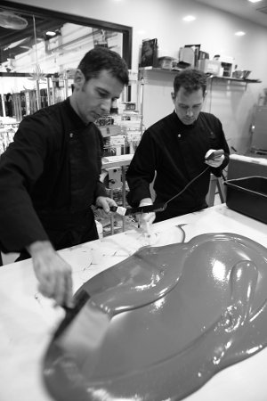 Laurent works the chocolate while an assistant probes the temperature