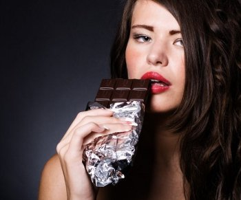 A young woman about to bite into a bar of dark chocolate