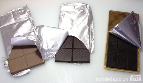 Three Lindt Excellence chocolate bars, with the foil peeled back to reveal the chocolate