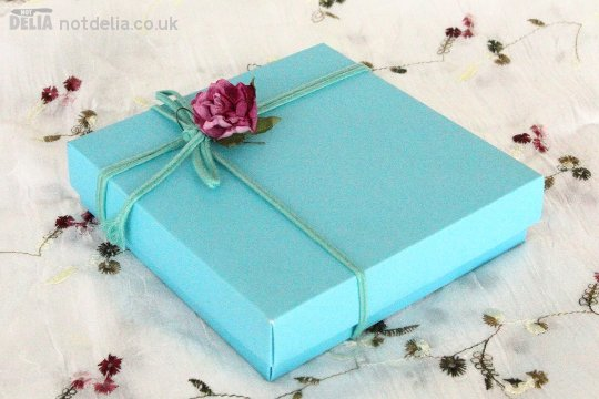 A gift box tied with pretty string with a flower on the end