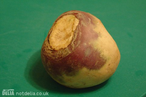 A whole swede or rutabaga on a chopping board