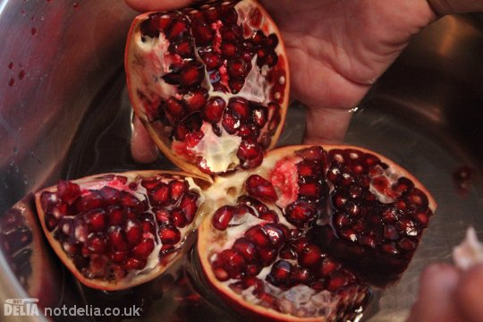A pomegranate scored and split into quarters over a bowl of water