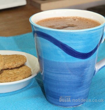 Hot chocolate in a mug with a small plate of Hob-Nobs