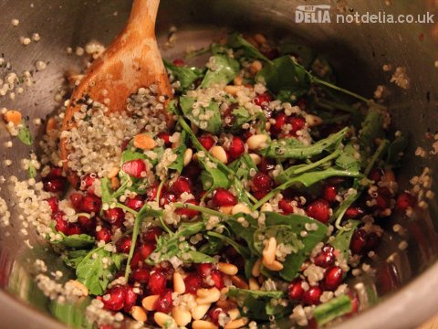 Pomegranate, quinoa and herb salad being mixed in a steel bowl