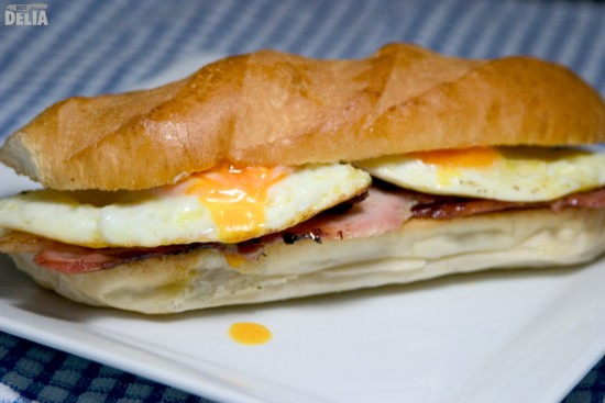 "A bacon and egg sandwich in a white ""sub"" roll"