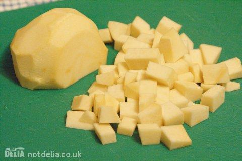 A diced swede or rutabaga on a chopping board