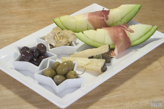 Not Delia's simple Parma ham platter with melon, Manchego cheese, artichoke hearts, and green and kalamata olives