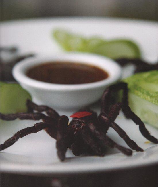 A deep-fried tarantula on a plate with dip