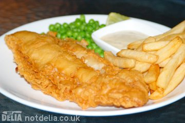 A plate of fish and chips with peas and tartar sauce