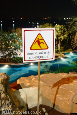 "A ""Dangerous"" sign in front of a low wall and a steep drop to a swimming pool"