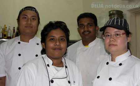 Four chefs in a clean kitchen smile at the camera
