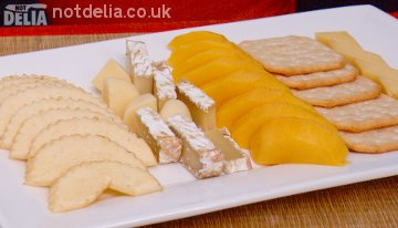A platter with cheese, slices of apple and mango and Tuc crackers