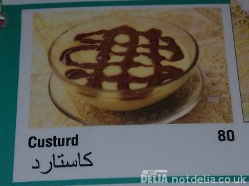 """A menu photo of a bowl of custard with an ugly brown sauce decoration, labelled """"Custurd"""""""