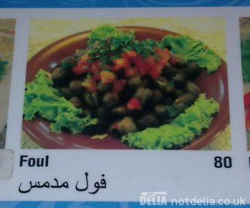 "A menu photo of a bowl of ful medames labelled ""Foul"""